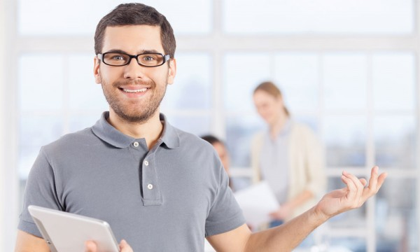 Easy sales coaching tips. Cheerful young businessman in casual wear holding digital tablet and smiling while his colleagues communicating on the background.