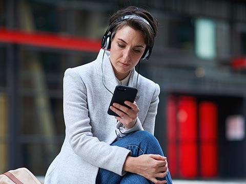 Woman sitting outside watching her smartphone with headphones